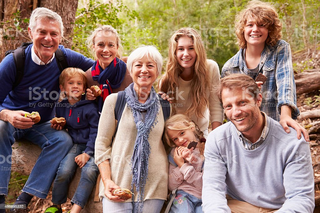 Multi-generation family with teens eating outdoors together stock photo