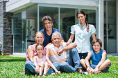 Multi-generation family with two children sitting in front house