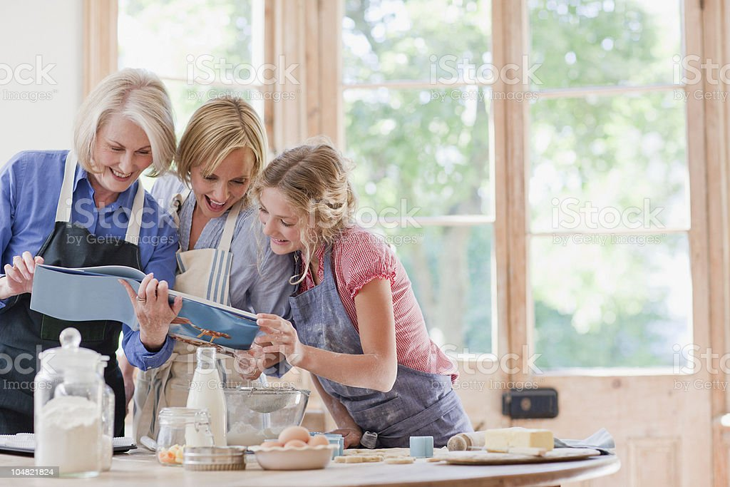 Multi-generation females looking at cookbook and baking in kitchen royalty-free stock photo