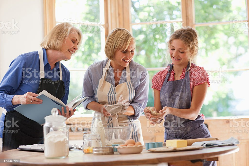 Multi-generation females looking at cookbook and baking in kitchen stock photo