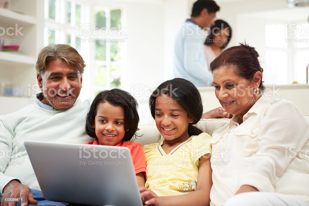 Multi-Generation Indian Family With Laptop stock photo