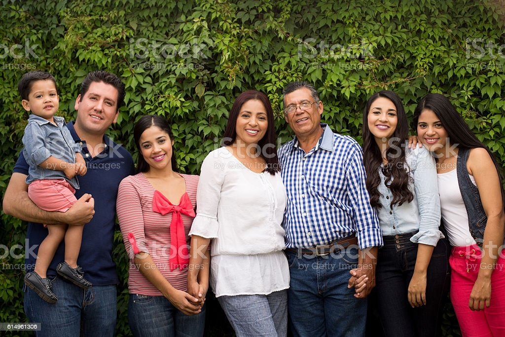 Multi-generation latin family standing and smiling stock photo