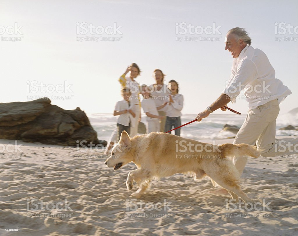 Multigenerational family at beach with dog royalty-free stock photo