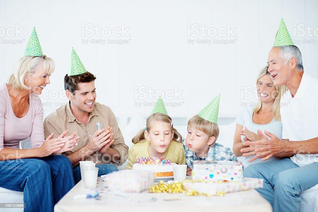 Multi-generational family celebrating young children's birthday royalty-free stock photo