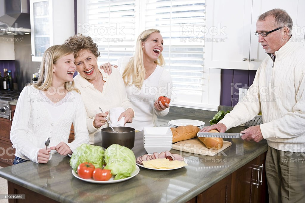 Multi-generational family making lunch in kitchen royalty-free stock photo