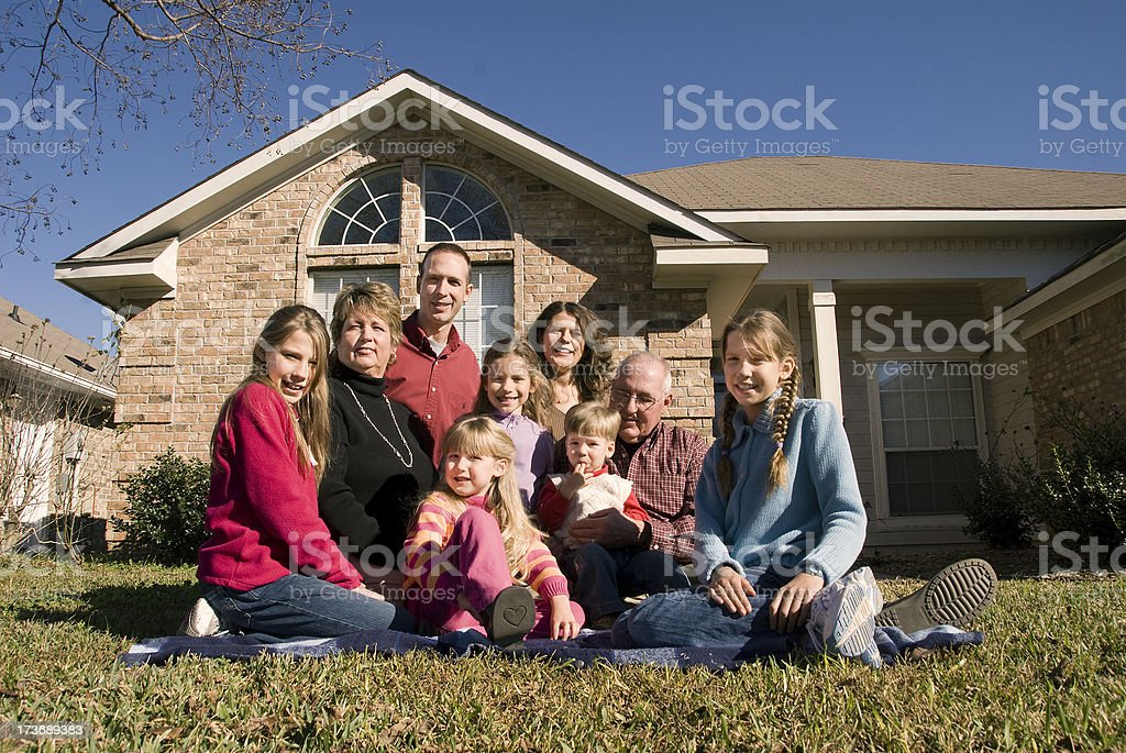 Multi-generational family sitting on front lawn royalty-free stock photo