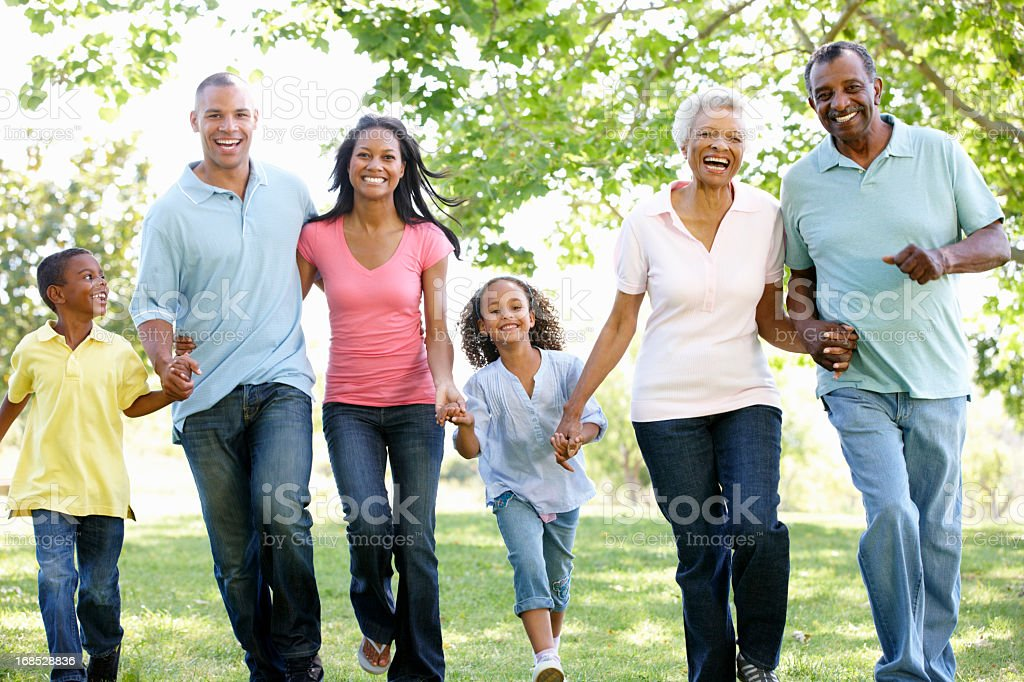 Multigenerational family walking in park holding hands royalty-free stock photo
