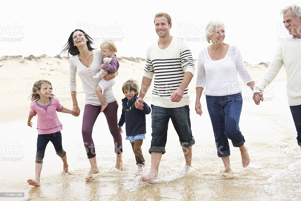 Multigenerational family walking on the beach stock photo