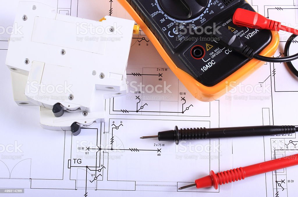 Multimeter and electric fuse on construction drawing stock photo
