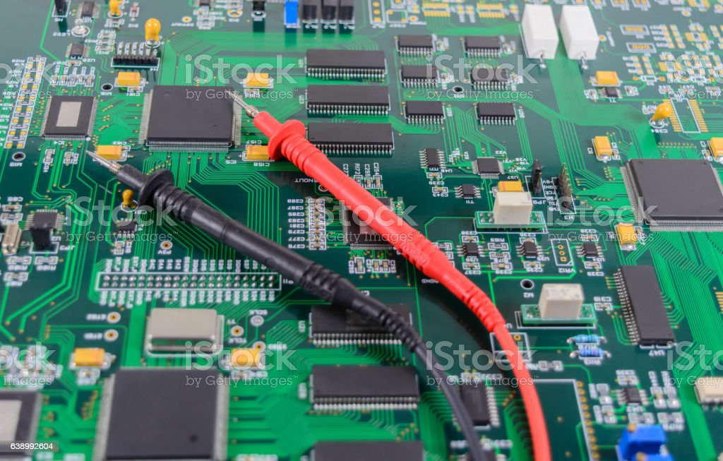 Multimeter test probes on printed circuit board stock photo