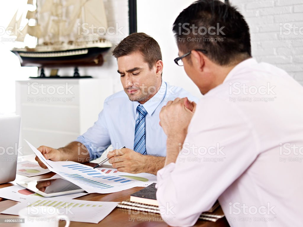 multinational businesspeople discussing sales performance in office stock photo