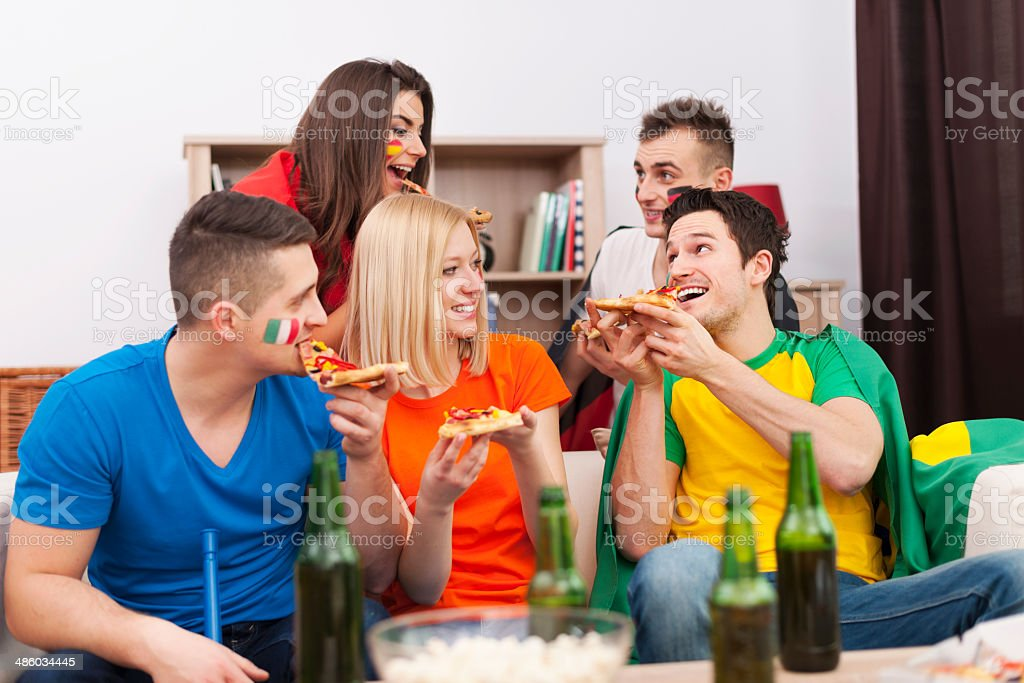 Multinational people eating pizza during the break in football match stock photo
