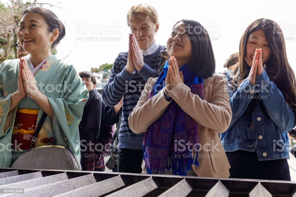 Multinational people praying in Japanese temples stock photo
