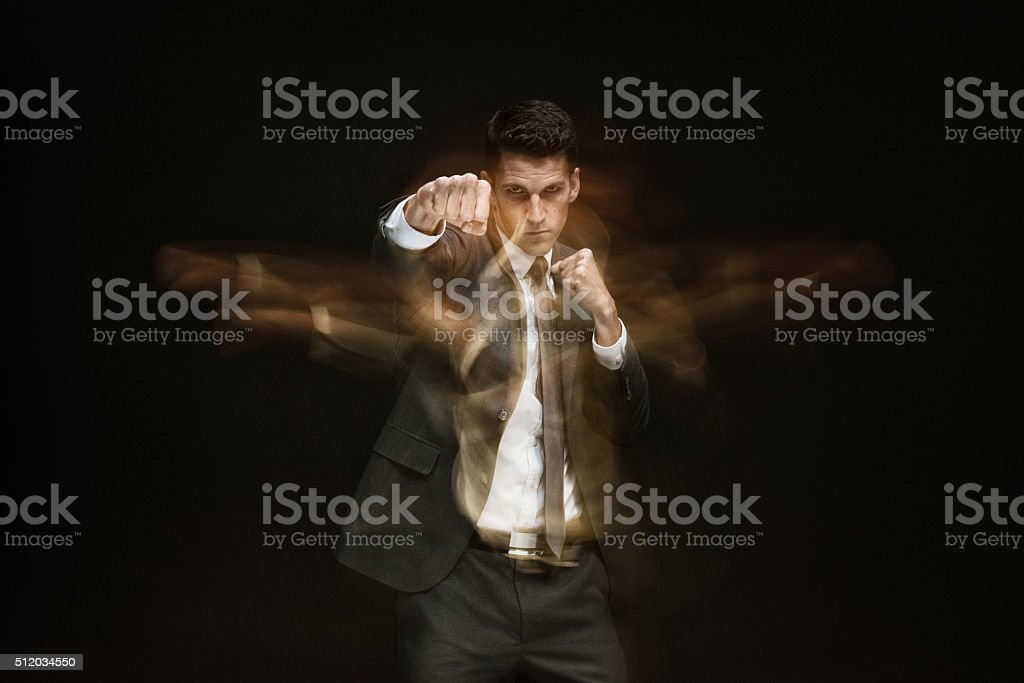 Multiple Exposure - Businessman punching stock photo