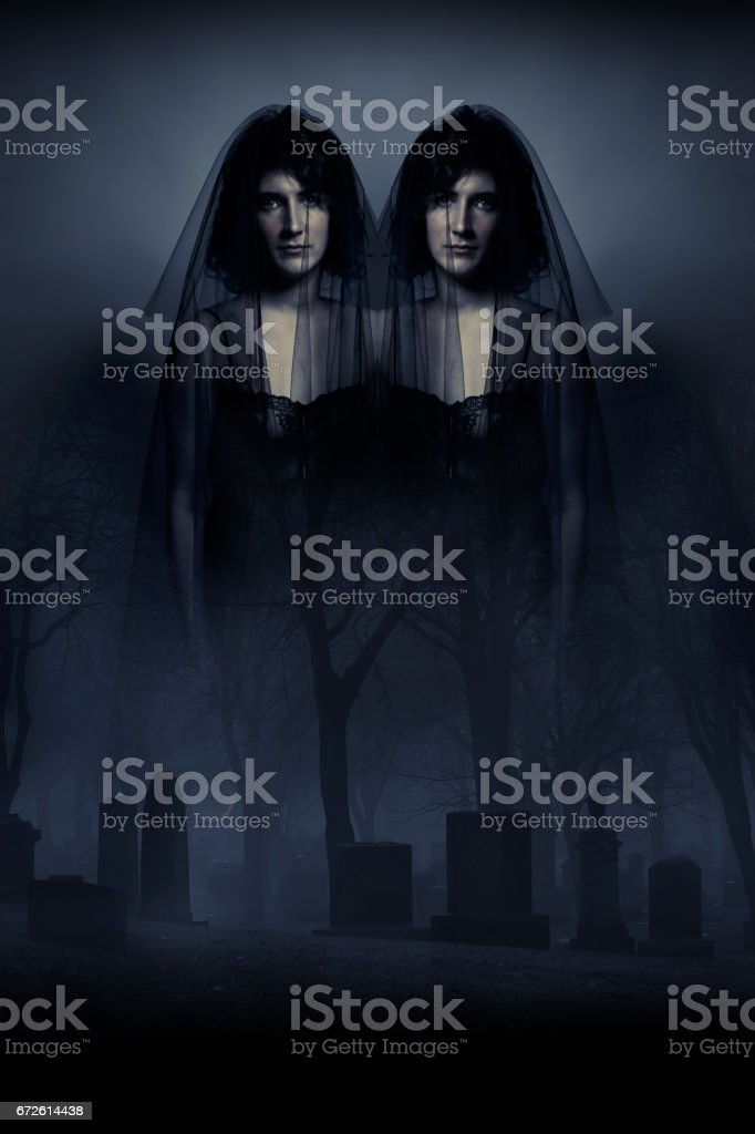 Multiple exposure image of Spooky identical twins haunting a foggy cemetery stock photo