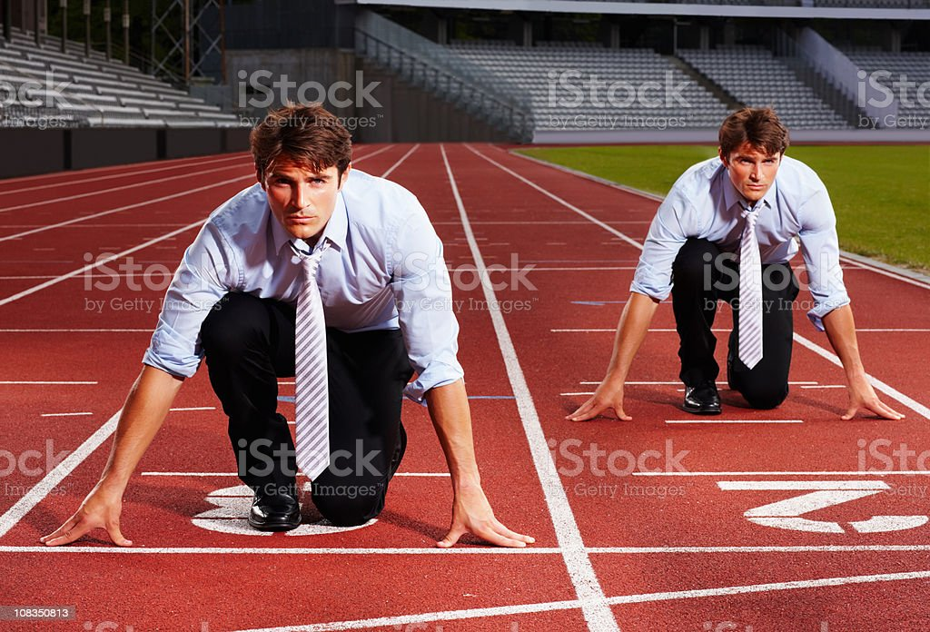 Multiple exposure of a business man getting ready for race royalty-free stock photo