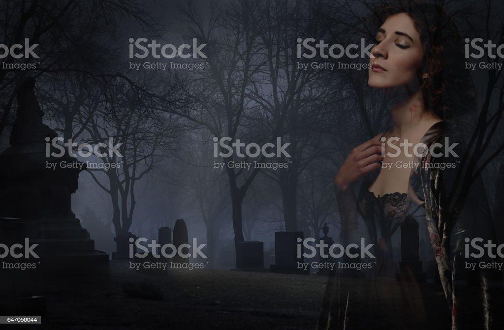 Multiple Exposure of a Female vampire in dark, foggy cemetery stock photo