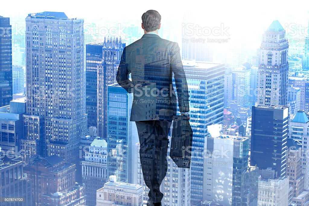 Multiple Exposure Of Businessman Walking Towards A Large City stock photo