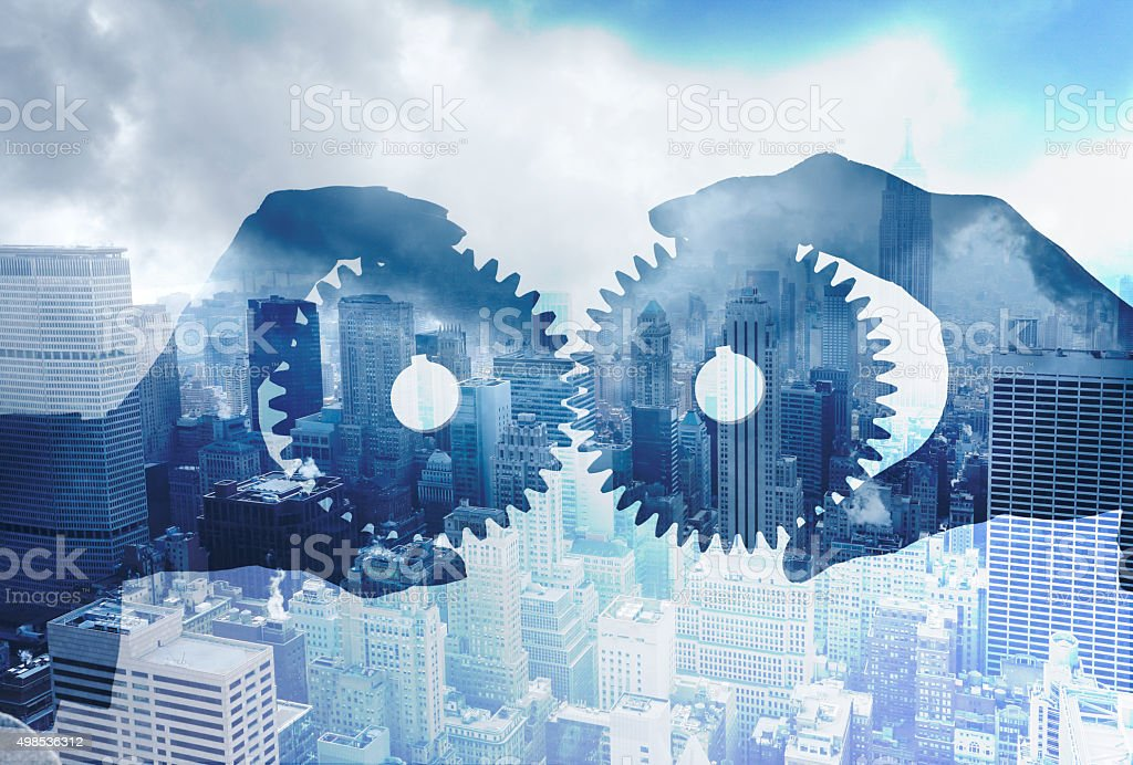 Multiple Exposure Of Businesspeople Interlocking Gears In Front OF City stock photo