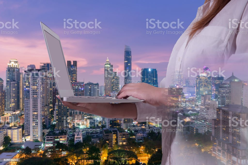 Multiple exposures of business concept with woman is using laptop and city skyline background. stock photo