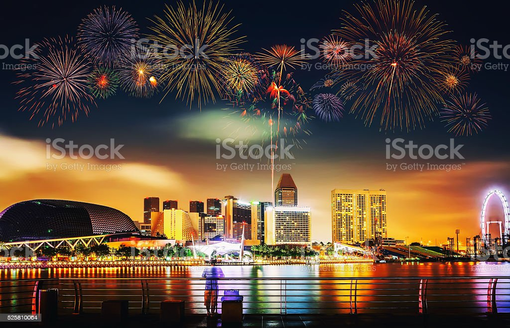Multiple fireworks exploding high in the sky over modern buildin stock photo