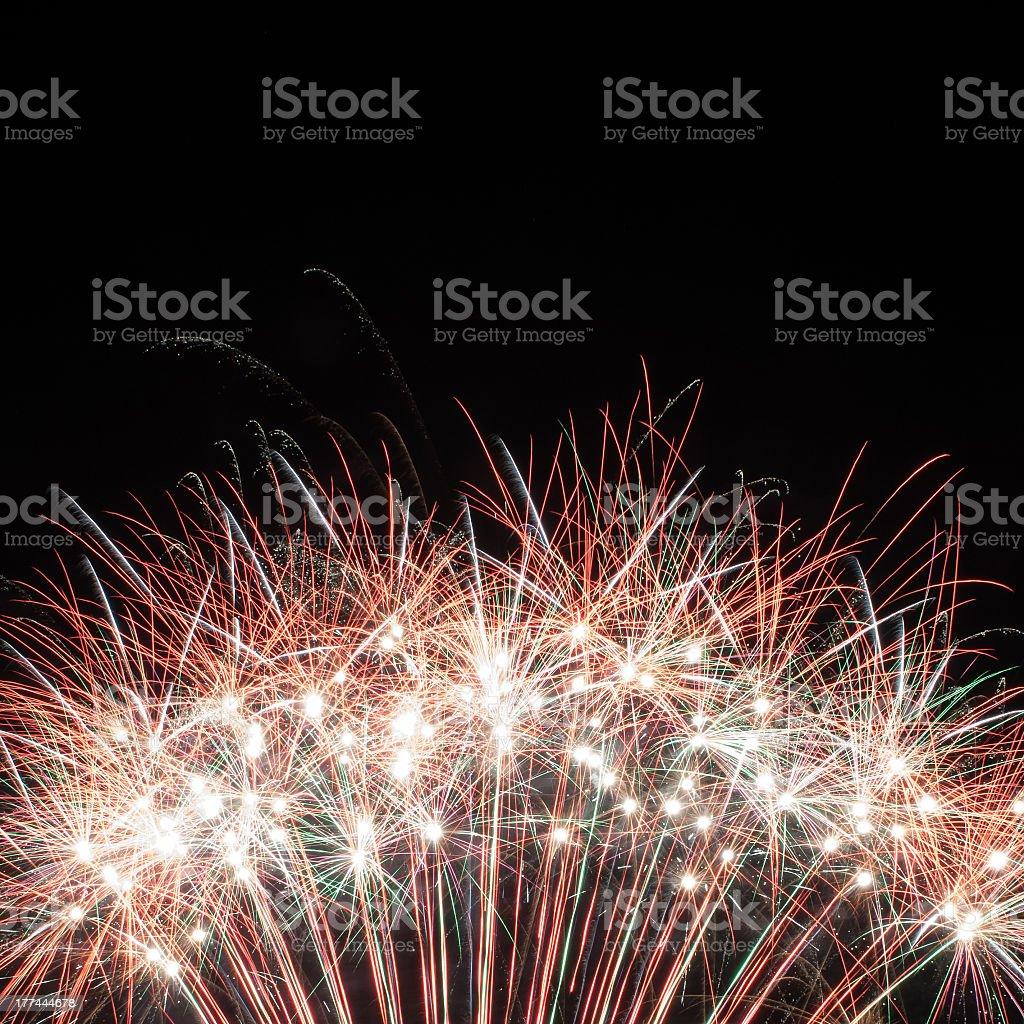 Multiple fireworks exploding over a dark background stock photo