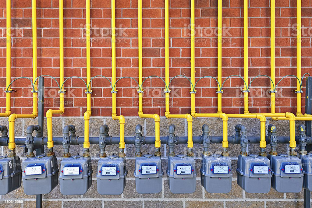 Multiple gas meters on red brick wall stock photo