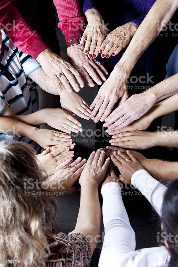 Multiple hands reaching towards a center royalty-free stock photo