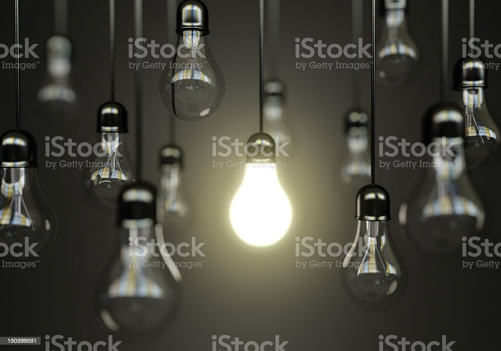 Multiple hanging light bulbs with one illuminated stock photo
