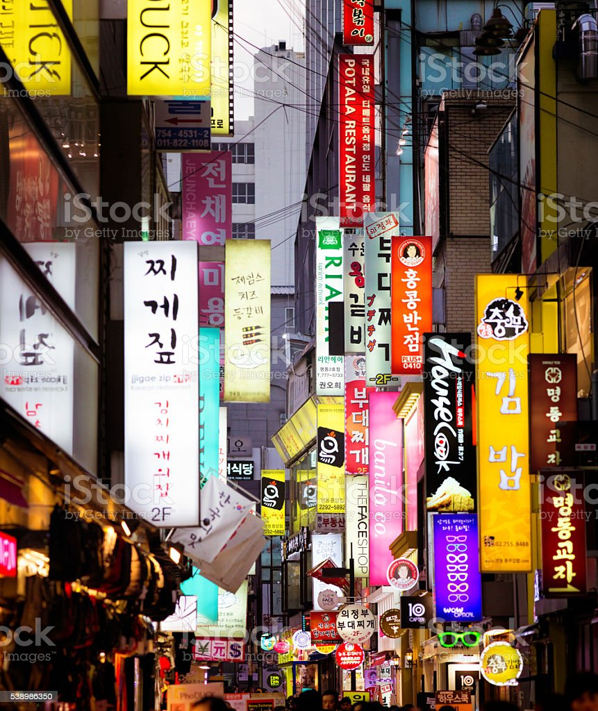 Multiple illuminated commercial signs in Seoul street at dusk stock photo