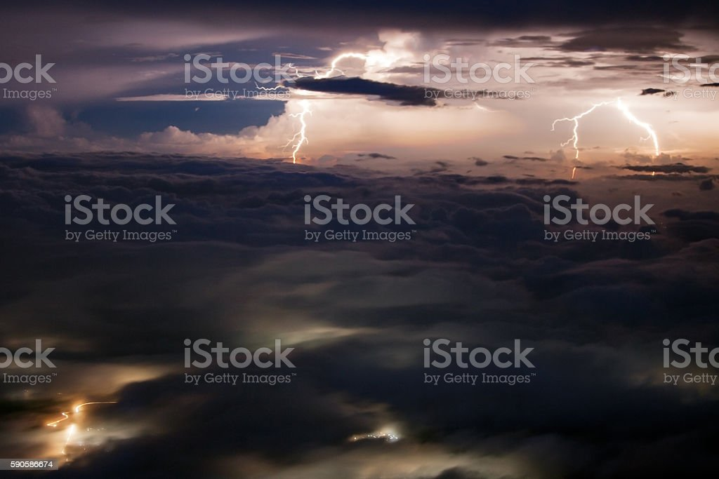 Multiple lightnings over the valley covered with clouds stock photo