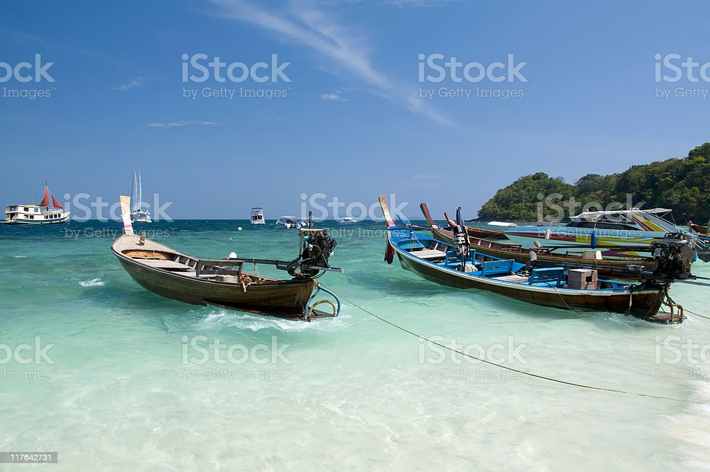 Multiple longtail boats at the beach royalty-free stock photo