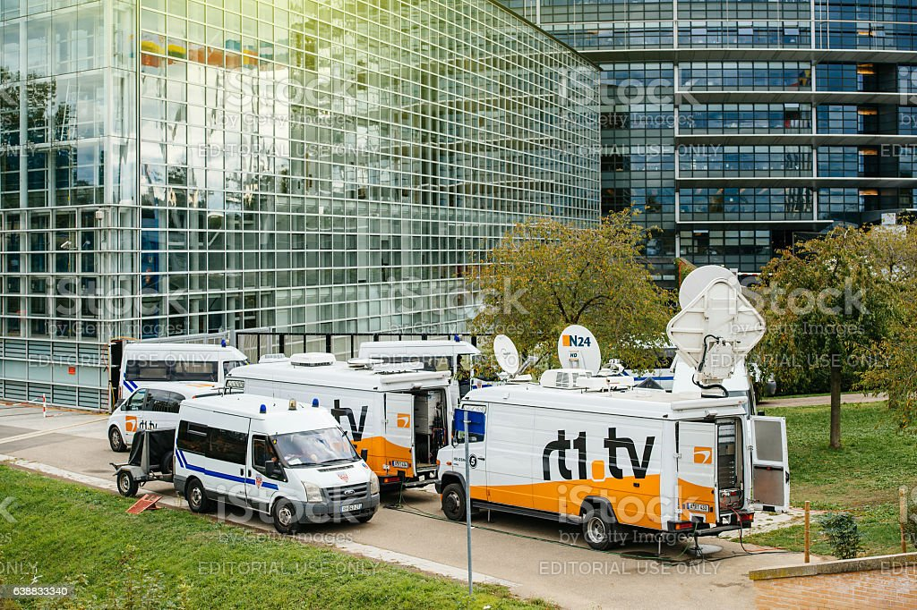 Multiple Media TV Trucks reporting live and police van surveilli stock photo