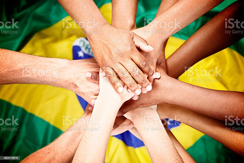 Multiple mixed hands pile onto Brazilian flag pledging loyalty royalty-free stock photo