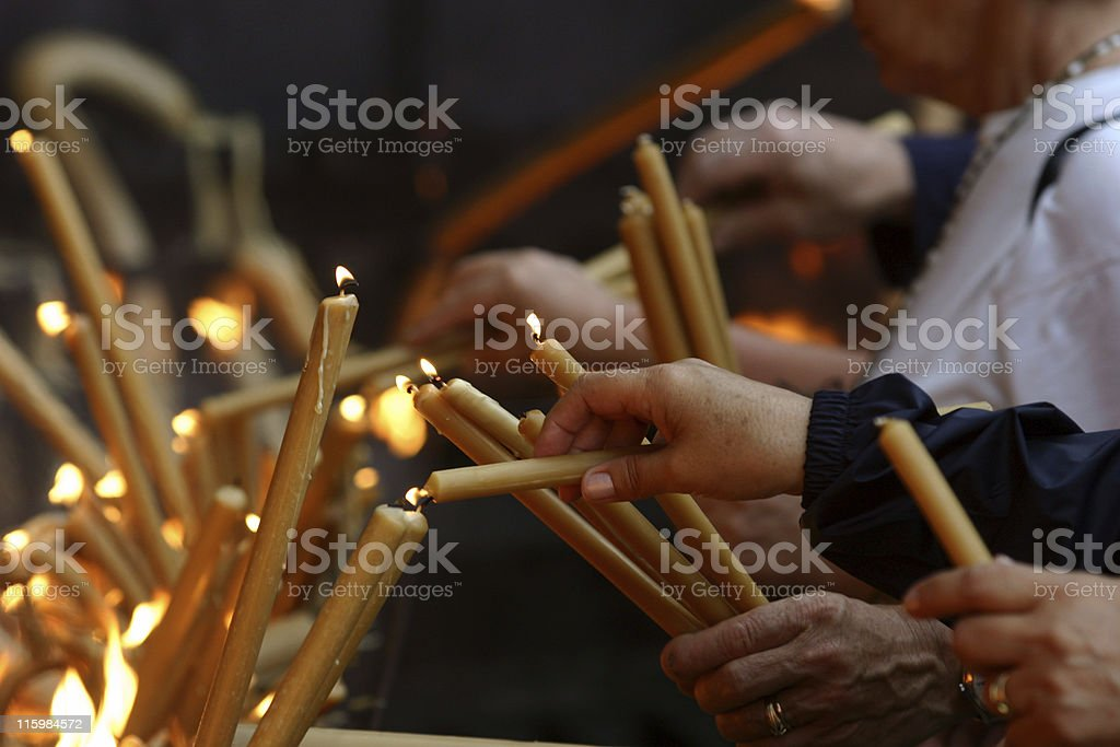 Multiple pairs of hands lighting gold candles stock photo