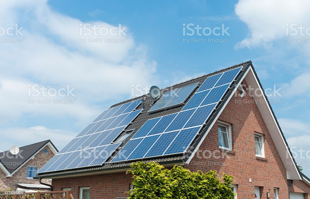 Multiple solar panels installed on a steep house roof stock photo