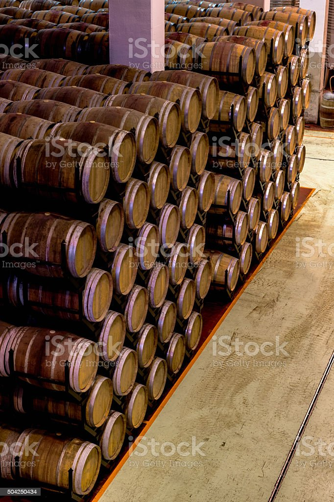 Multiple stocked barrels in a cellar during wine aging process stock photo