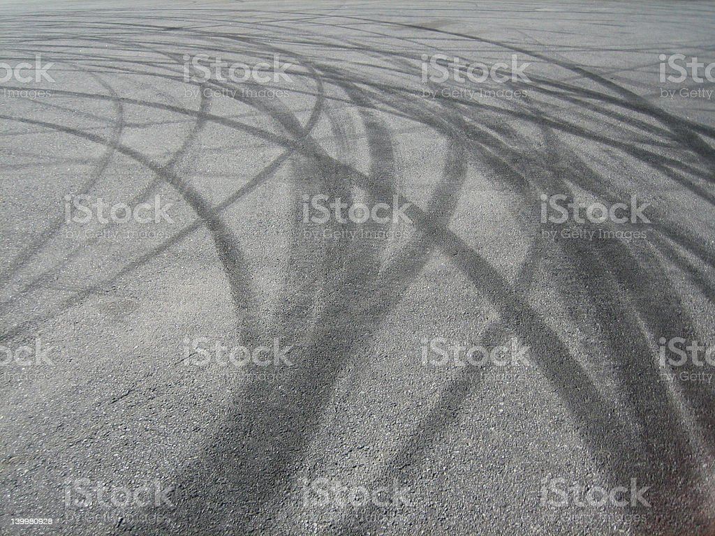 Multiple tire tracks on asphalt representing burning rubber royalty-free stock photo