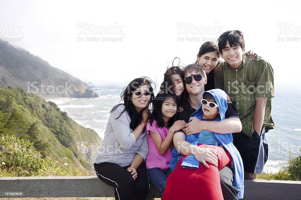 Multiracial amily of seven by the ocean shore stock photo