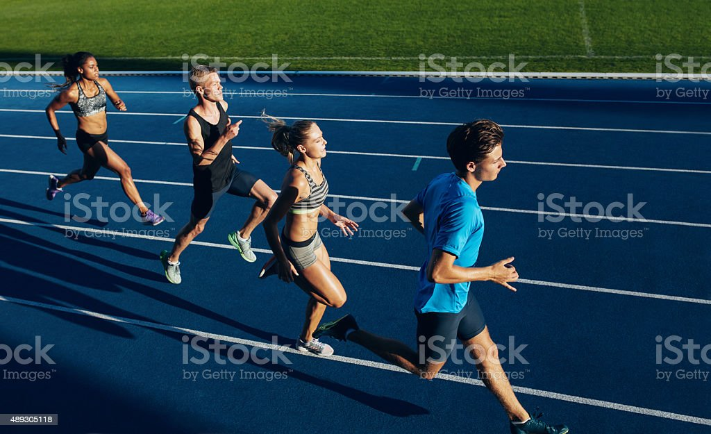 Multiracial athletes practicing running on racetrack stock photo