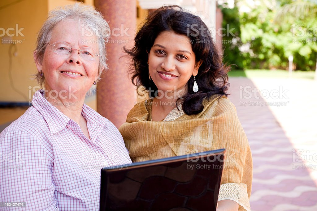 Multiracial Cheerful Caucasian Woman Indian Female Laptop Two People Horizontal royalty-free stock photo