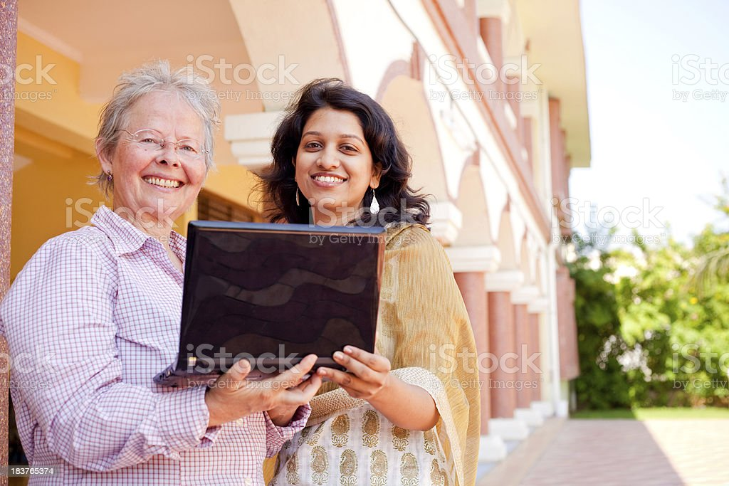 Multiracial Cheerful Caucasian Woman Indian Female Laptop Two People Outdoor royalty-free stock photo