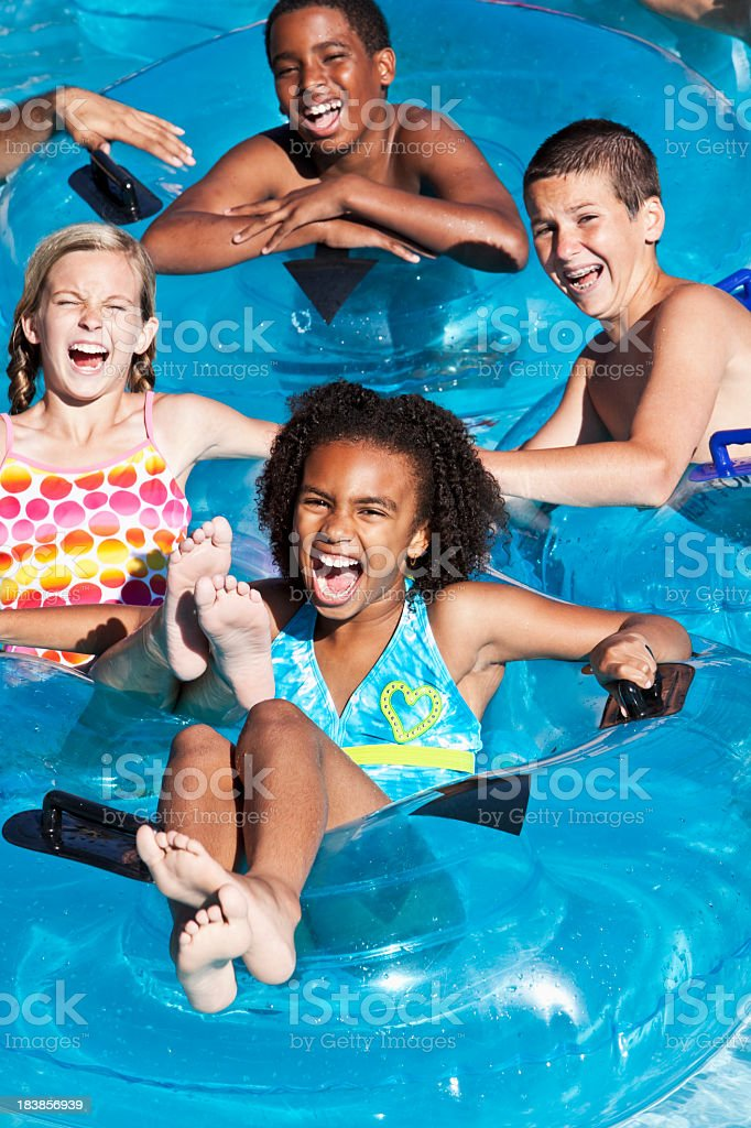 Multiracial children floating on innertubes at water park stock photo