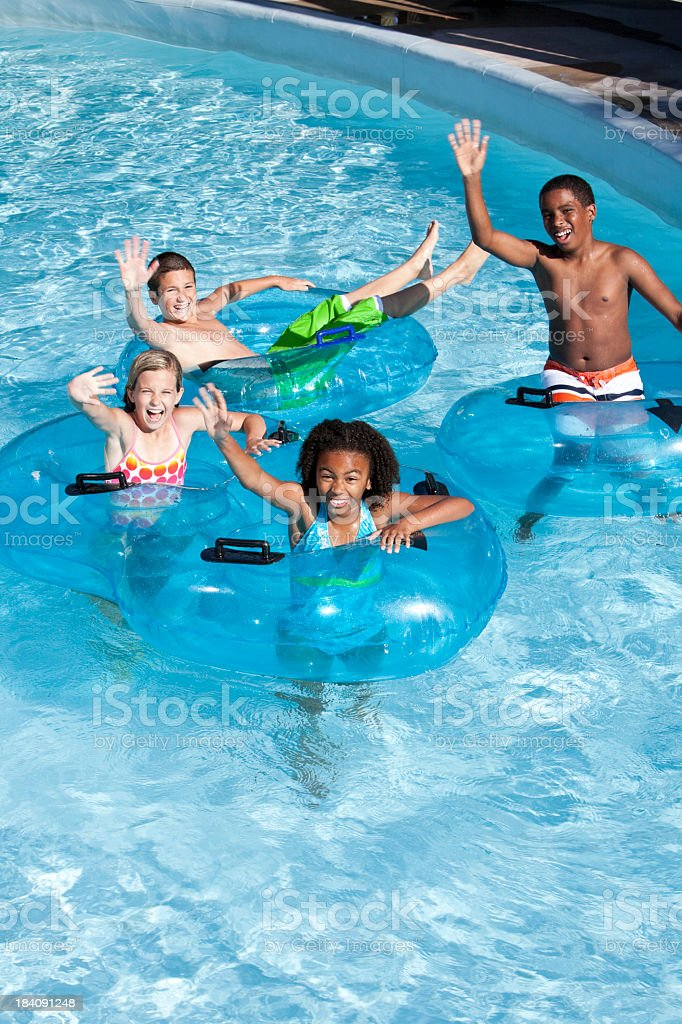 Multiracial children on innertubes at water park stock photo