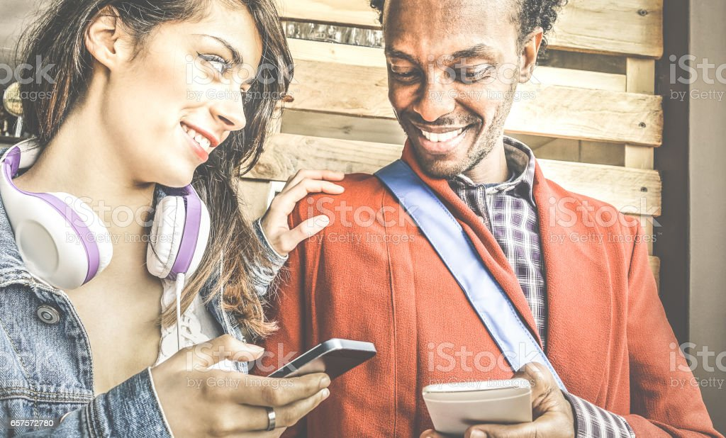 Multiracial couple flirting with smartphone numbers - Modern concept of mobile phone technology with happy people having fun - City urban lifestyle - Retro filter with focus on girl stock photo