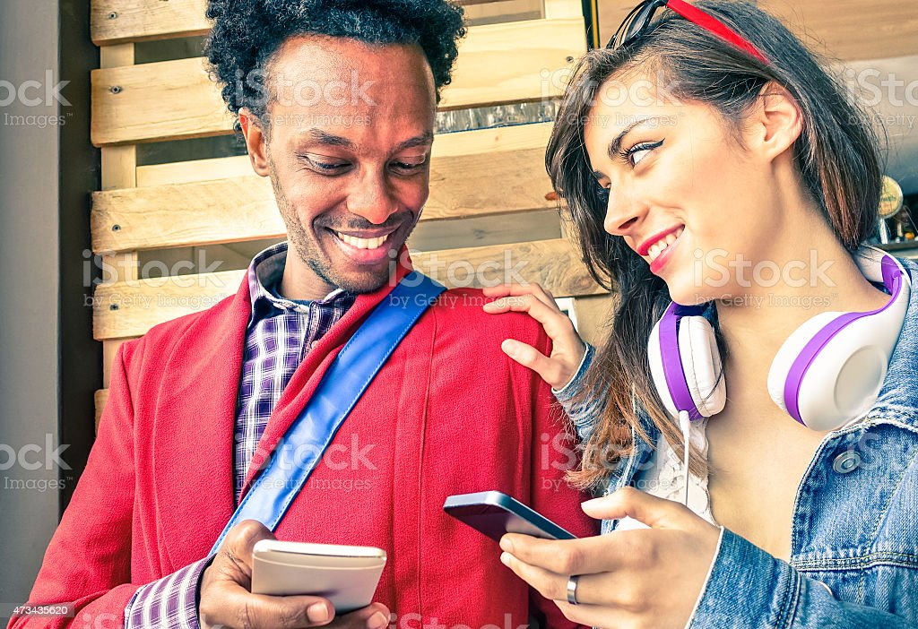 Multiracial couple flirting with smartphone numbers stock photo