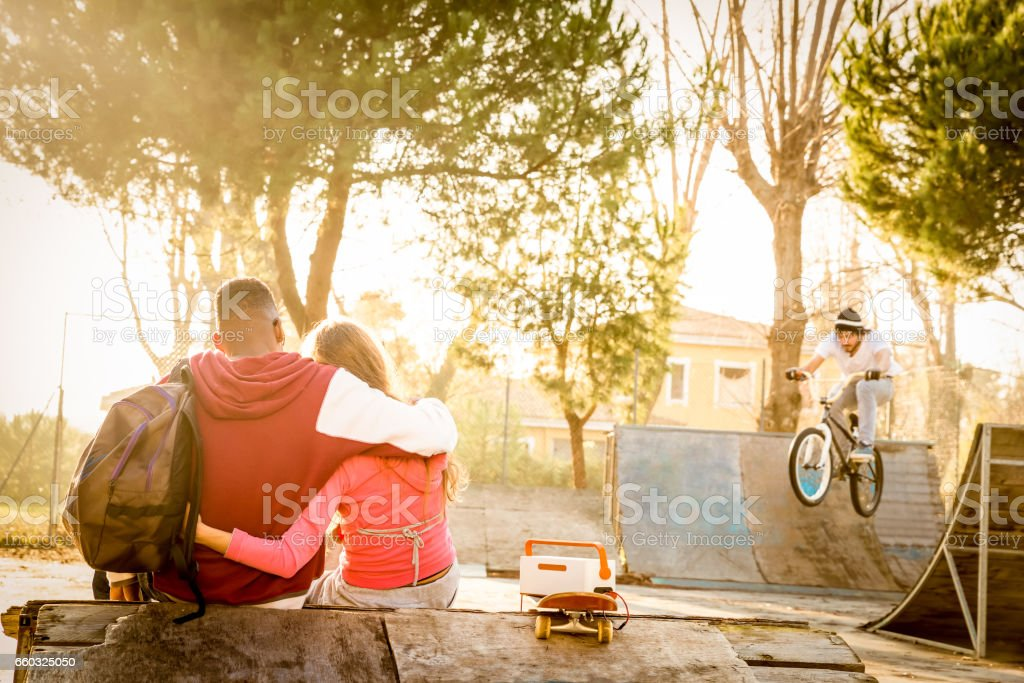 Multiracial couple in love sitting at skate park with music watching friends on bmx freestyle exhibition - Urban relationship concept with young people having fun outdoors - Warm contrasted filter stock photo
