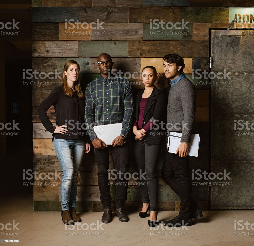 Multiracial creative team posing for camera in office stock photo