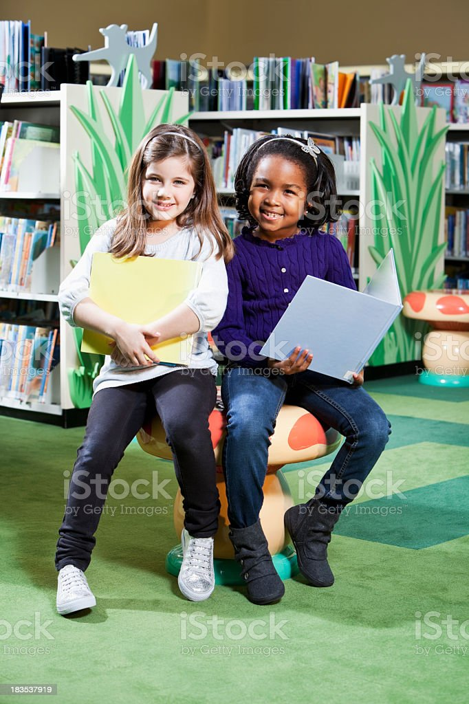 Multiracial elementary school children in the library stock photo