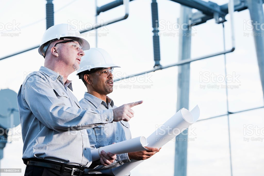 Multiracial engineers at industrial site looking up stock photo
